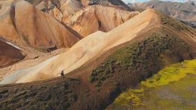Flyg- sikt av en turist som går på berget i Island Turist- manligt fotvandra på bergen stock video
