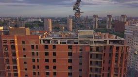 Flyg- sikt av ett nytt modernt hus under konstruktion med en blå tornkran, röd lykta på slutet av kranen, byggande materi stock video