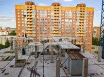 Flyg- sikt av ett nytt modernt hus under konstruktion med ett funktionsdugligt folk och en utrustning på taket på bakgrunden fotografering för bildbyråer