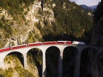 Flyg- sikt av ett rött drev som korsar den Landwasser viadukten i de schweiziska fjällängarna arkivfoto