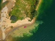 Flyg- sikt av ett rött fartyg på en sjö arkivbilder