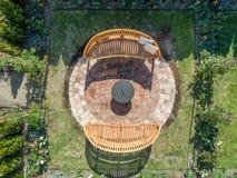 Flyg- sikt av ett stenlagt område med två hemtrevliga träbänkar och en brandbunke i din egen trädgård royaltyfria foton
