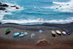 Flyg- sikt av färgrika fartyg på en svart sandstrand i Lanzarote, kanariefågelöar, Spanien royaltyfri foto