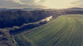 Flyg- sikt av floden som böjer över fält på solnedgången Arkivfoto
