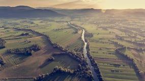 Flyg- sikt av floden som böjer över fält på solnedgången Royaltyfria Foton