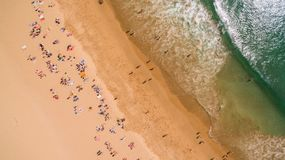 Flyg- sikt av folk som vilar på en härlig strand nära havet, Portugal arkivfoto