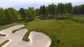 Flyg- sikt av golfare som spelar på sättande gräsplan Yrkesmässiga spelare på en grön golfbana royaltyfri fotografi