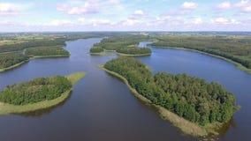 Flyg- sikt av gröna öar och moln på den soliga morgonen för sommar Masurian sjöområde i Polen Under av världen från över lager videofilmer