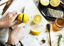 Flyg- sikt av händer med den bitande citronen för kniv Royaltyfri Fotografi