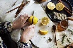 Flyg- sikt av händer med den bitande citronen för kniv Royaltyfria Bilder
