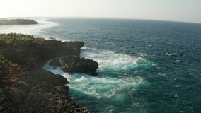 Flyg- sikt av havet med vågor som krossar över Nusa Dua-klippor i Bali arkivfilmer
