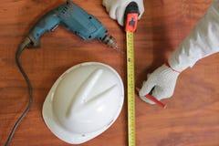 Flyg- sikt av hjälpmedel av wood arbete på träbakgrund Mäta bandet, säkerhetshjälm, elektrisk drillborr Royaltyfria Bilder