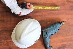 Flyg- sikt av hjälpmedel av wood arbete på träbakgrund Mäta bandet, säkerhetshjälm, elektrisk drillborr arkivbilder