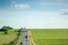 Flyg- sikt av huvudvägithbilar, lastbilgräsplanfält och windmil Fotografering för Bildbyråer