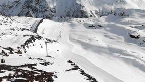 Flyg- sikt av kabelbilen och att skida lutningar i de höga bergen av Kaukasuset i semesterorten av Elbrus i vintern lager videofilmer