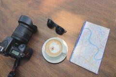 Flyg- sikt av kameran, kaffekoppen, översikten och sunglass på den gamla träöverkanten Arkivfoton