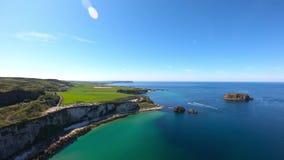 Flyg- sikt av klippor och turkosAtlantic Ocean vatten, Carrick en Rede repbro i nordligt - Irland stock video
