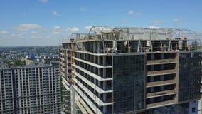 Flyg- sikt av konstruktionsplatsen med Team Of Builders On Roof som diskuterar plan av projektet stock video