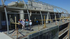 Flyg- sikt av konstruktionsplatsen med Team Of Builders On Roof som diskuterar plan av projektet lager videofilmer