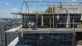 Flyg- sikt av konstruktionsplatsen med Team Of Builders On Roof som diskuterar plan av projektet arkivfilmer