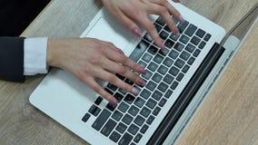 Flyg- sikt av kvinnamaskinskrivning på bärbara datorn Förlagt på träskrivbordet arkivfilmer