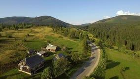 Flyg- sikt av landskapet med den lilla byn i berg stock video
