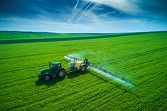Flyg- sikt av lantbruktraktoren som plogar och besprutar på fält royaltyfri bild