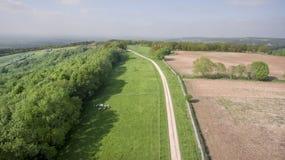 Flyg- sikt av lantgårdfält, ängar, vandringsled överst av kullen Arkivbilder