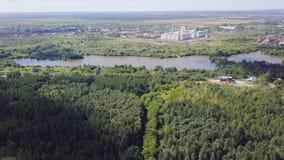Flyg- sikt av lilla staden nära skoggemet Flyg- sikt av staden i ett skogsbevuxet område med floden Royaltyfri Fotografi