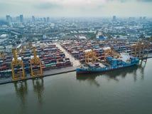 Flyg- sikt av logistiken och trans. av behållarelastfartyget och Crane Bridge med byggande cityscapebakgrund import arkivbild