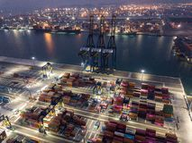 Flyg- sikt av logistiken och trans. av behållarelastfartyget och Crane Bridge med byggande cityscapebakgrund import royaltyfri foto