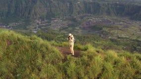 Flyg- sikt av mannen med en kamera överst av en klippa som förbiser bergen Kameraman ser soluppgången på stock video
