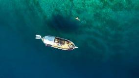 Flyg- sikt av mansimning i havet bredvid fartyget arkivfilmer