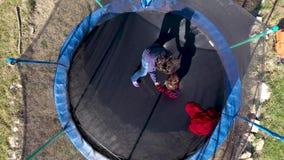 Flyg- sikt av modern med hennes dotter som har gyckel och hoppar p? trampolinen med surret stock video