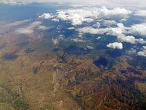Flyg- sikt av moln och berglandskapet från ett flygplan i stratosfären Arkivfoton