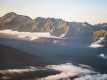 Flyg- sikt av moln under bergen under solnedgång Royaltyfria Bilder