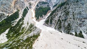 Flyg- sikt av mudflowen med snö som är hög i de alpina bergen Royaltyfri Fotografi