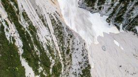 Flyg- sikt av mudflowen med snö som är hög i de alpina bergen, bästa sikt Arkivbild