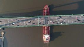 Flyg- sikt av oljetankerskeppet som passerar under en upphängningbro som är full av bilar lager videofilmer