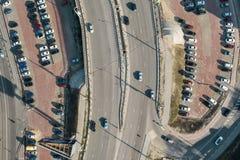 Flyg- sikt av parkeringsplatsen med den parkerade bilar och asfaltbrovägen med trafik, bästa sikt från surret royaltyfri foto
