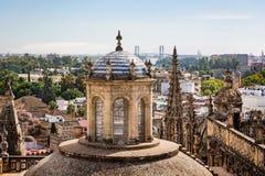 Flyg- sikt av Seville domkyrkor utsmyckat tak och kupoler med staden och den hundraårs- bron i bakgrund i Seville, Spanien royaltyfri foto