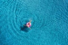 Flyg- sikt av simning för ung kvinna i havet med genomskinligt vatten arkivbild
