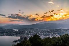 Flyg- sikt av sjön Lugano som omges av berg och aftonstaden Lugano på under den dramatiska solnedgången, Schweiz, Arkivbild