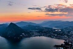 Flyg- sikt av sjön Lugano som omges av berg och aftonstaden Lugano på under den dramatiska solnedgången, Schweiz, fjällängar Arkivfoton