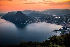 Flyg- sikt av sjön Lugano som omges av berg och aftonstaden Lugano på under den dramatiska solnedgången, Schweiz, fjällängar Royaltyfri Bild