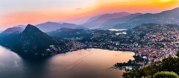 Flyg- sikt av sjön Lugano som omges av berg och aftonstaden Lugano på under den dramatiska solnedgången, Schweiz, fjällängar Royaltyfri Foto