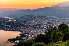 Flyg- sikt av sjön Lugano som omges av berg och aftonstaden Lugano på under den dramatiska solnedgången, Schweiz, fjällängar Arkivbilder