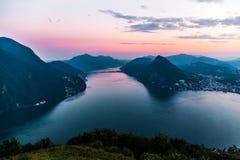 Flyg- sikt av sjön Lugano som omges av berg och aftonstaden Lugano på under den dramatiska solnedgången, Schweiz, fjällängar Arkivbild