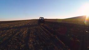Flyg- sikt av skördfält med att odla traktoren Bonde som plogar stubbåkern lager videofilmer
