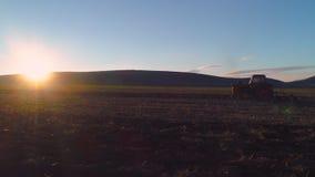 Flyg- sikt av skördfält med att odla traktoren Bonde som plogar stubbåkern stock video